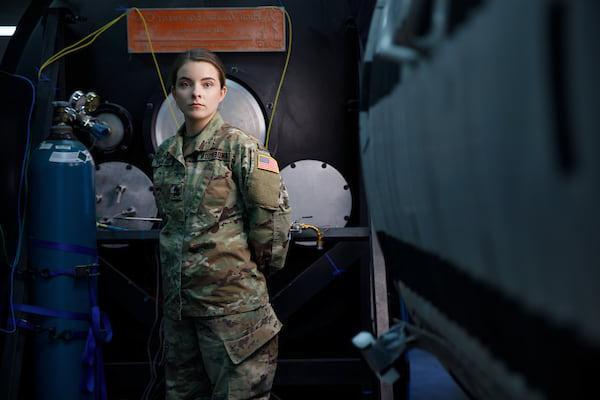 一名身穿军装的学生站在工业设备中间