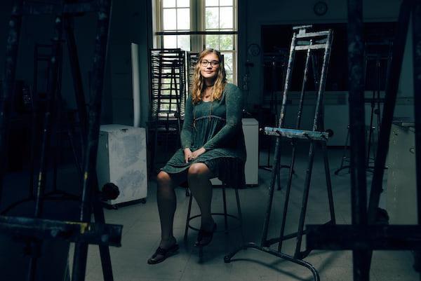 一个学生坐在画架和艺术用品之间