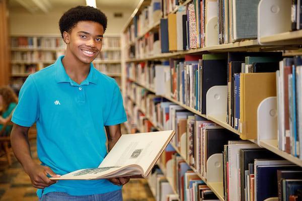 一个早期的大学生正在浏览图书馆的藏书