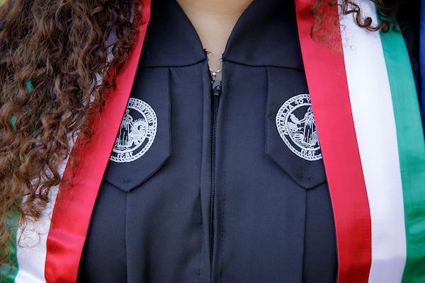 一名学生在毕业典礼上戴着印有家乡颜色的横幅